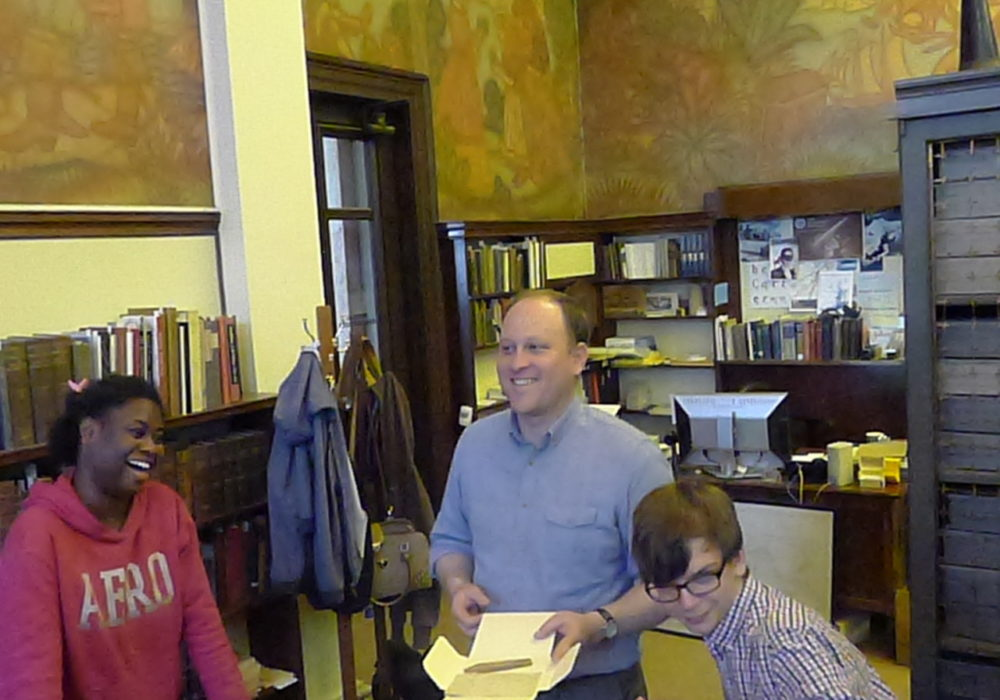 Jordan Goffin, Head Curator of Special Collections, and two students looking at items in Special Collections