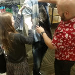 A visual merchandiser and a Teen Squad participant dress a mannequin