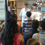 Teens talking to a chef as part of a Teen Squad culinary arts program