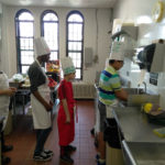 Teens wearing chef hats washing their hands in a kitchen