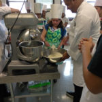 A Teen Squad participant helps a chef from the Genesis Center add ingredients to a dish