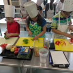 Teen Squad culinary arts program participants dice red and green peppers in a kitchen