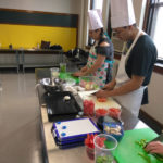 Teen Squad culinary arts program participants dice onions and peppers in a kitchen