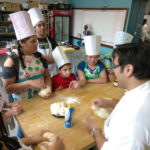 Teen Squad program participants knead dough in a kitchen
