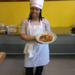 A Teen Squad participant holding a dish she prepared as part of the culinary arts program