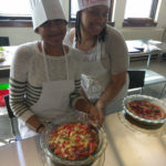Two Teen Squad members posing with quiches they prepared as part of the culinary arts program