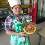 A Teen Squad member holding up a quiche she prepared as part of the culinary arts program