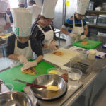 Teen Squad members chopping ingredients in a kitchen as part of the culinary arts program