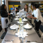 Teen Squad members prepare a dining table with place settings