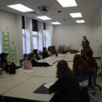 Teen Squad members listen to a mentor discuss dress design