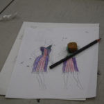 A sketch of a flapper style dress with a sketching pencil and an eraser on top of it
