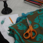 Brown and teal colored fabric near a sketch of 1920s flapper style dresses