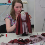A Teen Squad member works on a pink dress with a red cape on a miniature dress form
