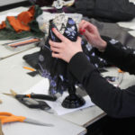 A Teen Squad member works on a black and violet colored dress on a miniature dress form