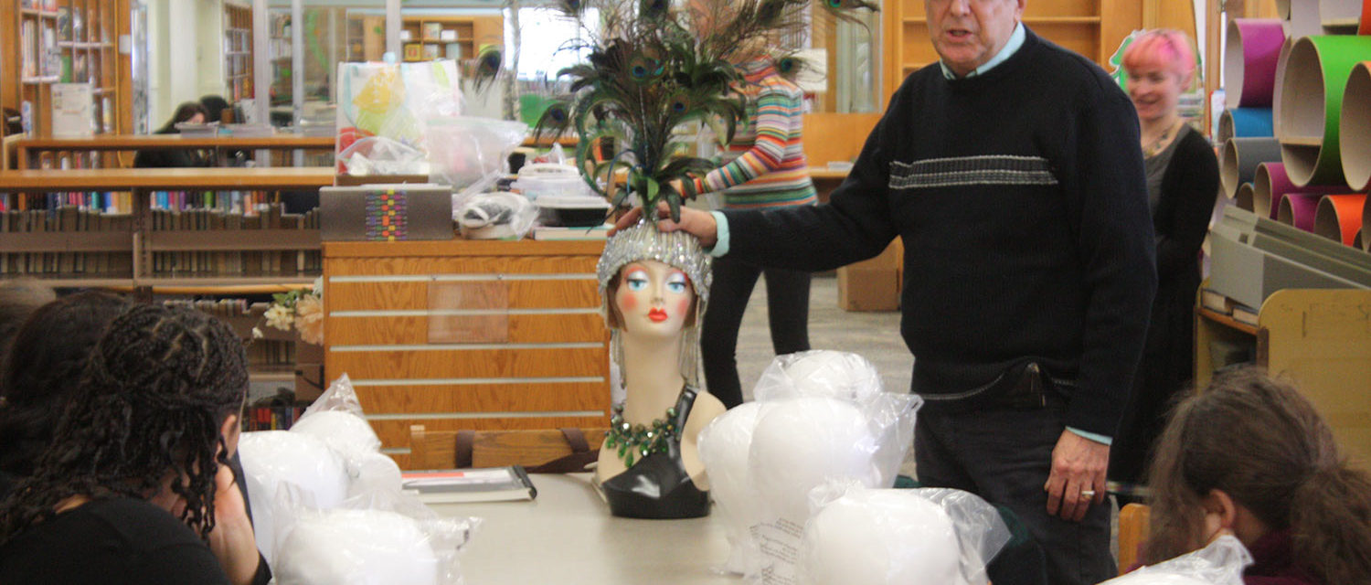 A mentor displaying an elaborate peacock headdress on a mannequin head