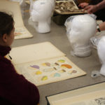 A Teen Squad member looks at historic headdress illustrations