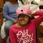 A Teen Squad member wearing a headdress she made as part of the Teen Squad program