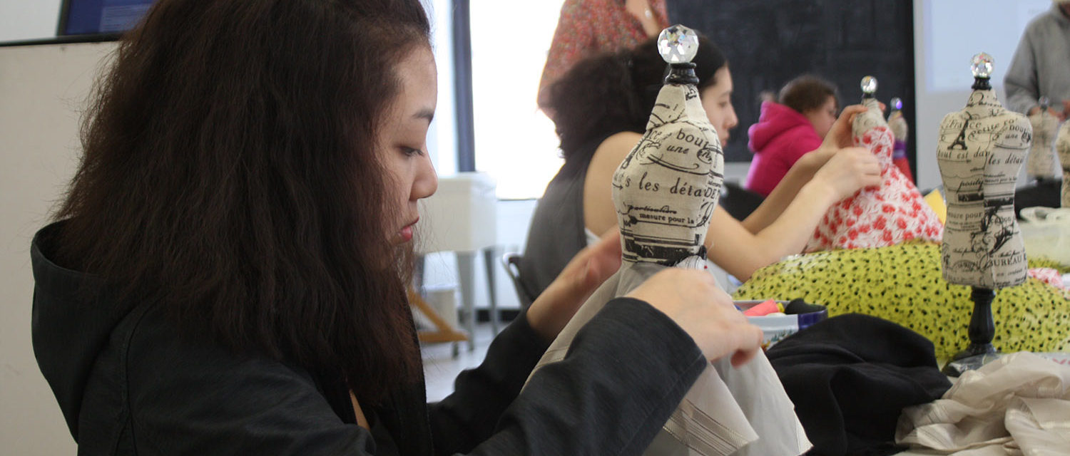 A Teen Squad member prepares a dress on a miniature dress form
