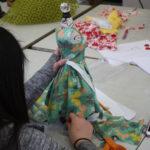 A Teen Squad member prepares a dress on a miniature dress form