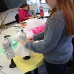 A Teen Squad member works on a dress on a miniature dress form