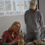 A mentor works with a Teen Squad member on a dress on a miniature dress form