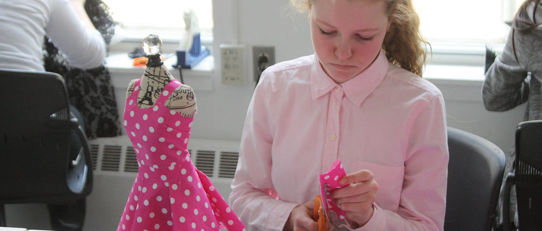 A teen squad member cuts pink polka dot fabric