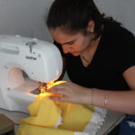 A Teen Squad member sews fabric using a sewing machine