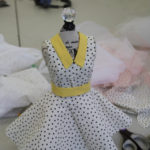 A miniature dress form with a black and white polka dress on it.