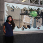 A Teen Squad member posing with a window display at Providence Public Library