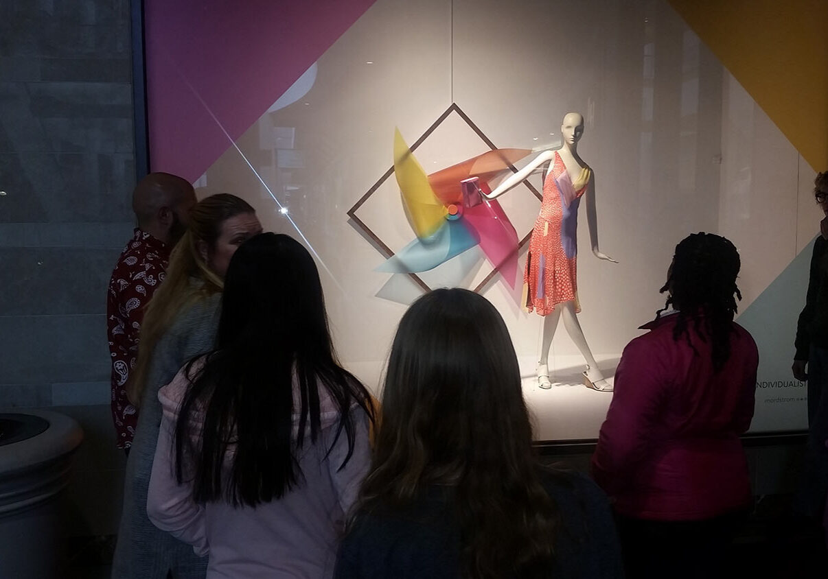 Teen Squad members look at a window display at Nordstrom