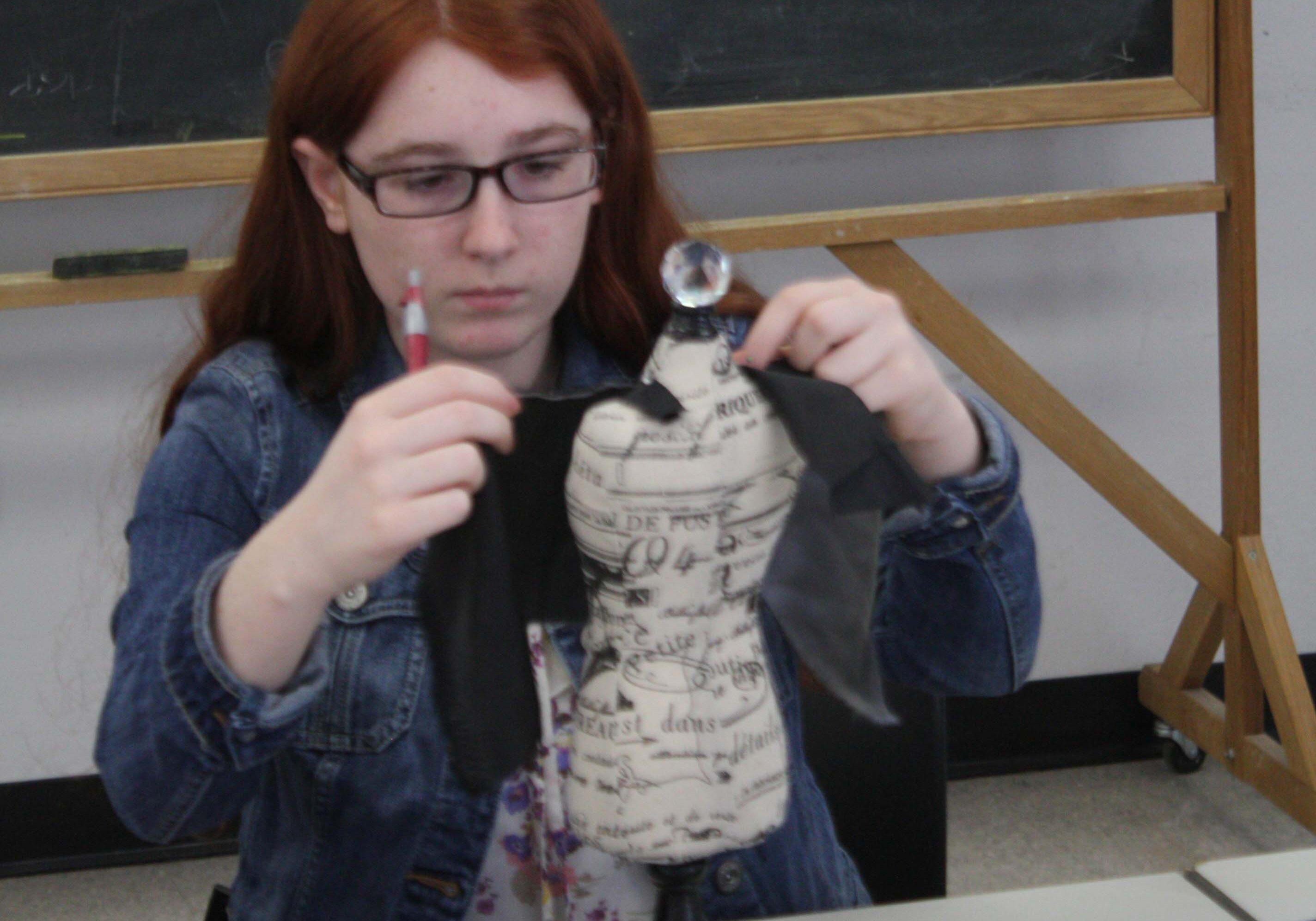 A participant in a teen program designs a dress on a miniature dress form