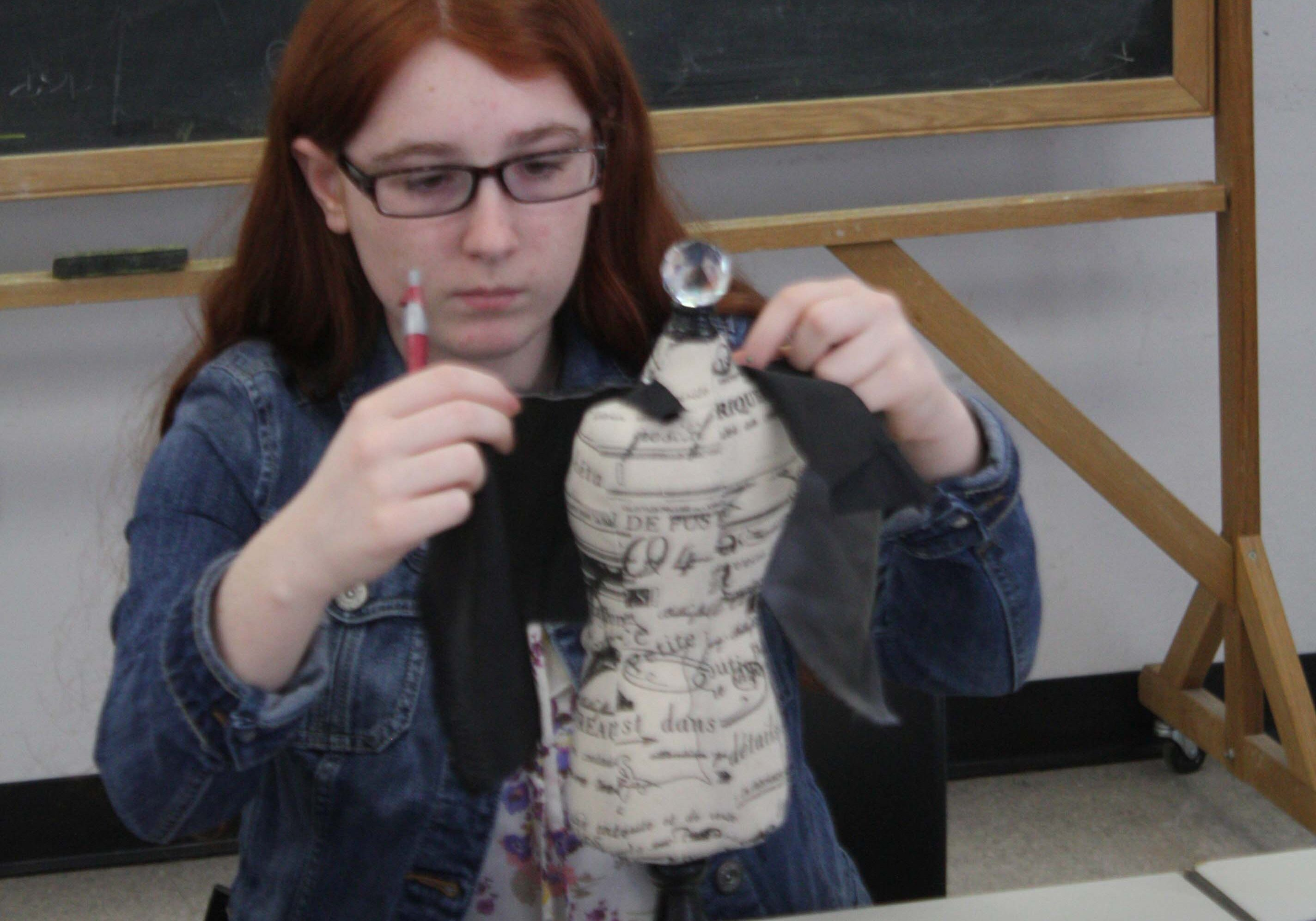 A participant in a teen program designs a dress on a miniature dress form